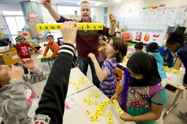 Apprendre par le jeu pourrait être la devise dans la classe combinée de 1re et 2e année. L'enseignant, Michel-Yves Lepage, invente de petits jeux, comme ici avec des lettres inscrites sur des cubes, pour aider les enfants à apprendre certaines notions de français.Photo: Alain Roberge, La Presse